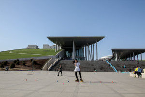 Young woman skates outside the Inner Mongolia Museum, another example of massive infrastructure designed to promote unity in regional areas.