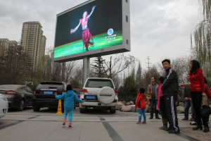 A young girl copies a dancer on a video billboard in a park on the banks of the Yellow River in Lanzhou, Gansu Province, North West China