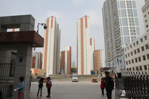 A school yard surround by apartment towers. Security at schools has been tightened after a number of attacks. This school had armed guards and crash resistant barriers. Xining, Qinghai province, Western China