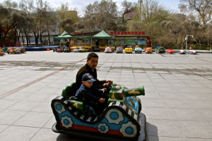 Father and son enjoy a ride in People's Park, Ürümqi.